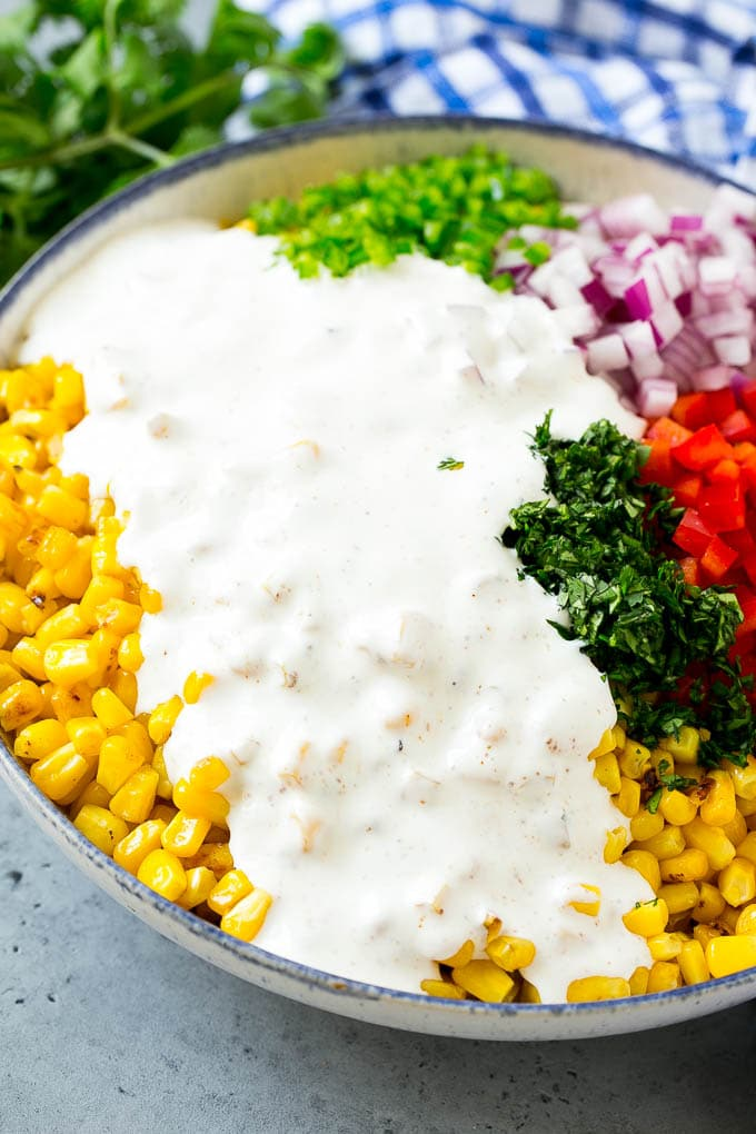 A bowl of corn and vegetables topped with a creamy dressing.