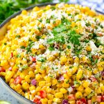 A bowl of Mexican corn salad topped with cotija cheese and fresh cilantro.