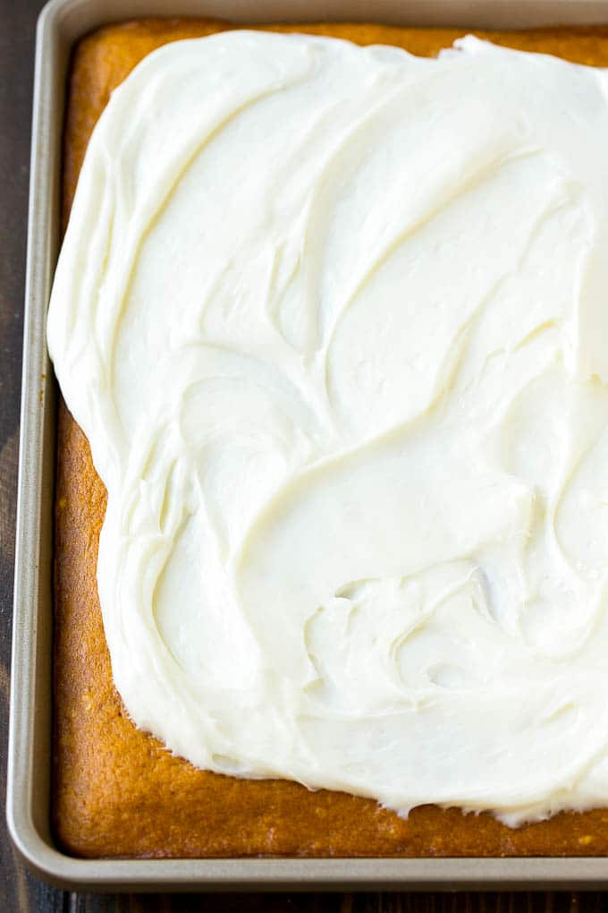 A pan of pumpkin bars with cream cheese frosting on top.