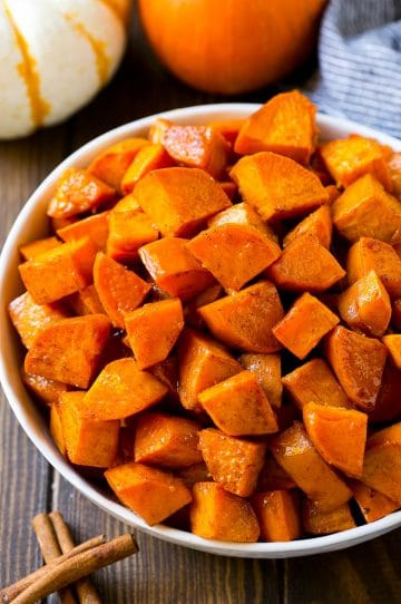 A bowl of maple roasted sweet potatoes with cinnamon and butter.