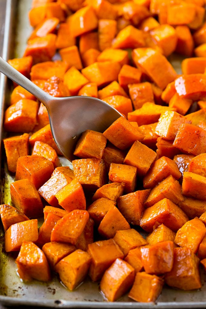 A sheet pan of baked sweet potatoes flavored with maple and cinnamon, with a serving spoon in them.