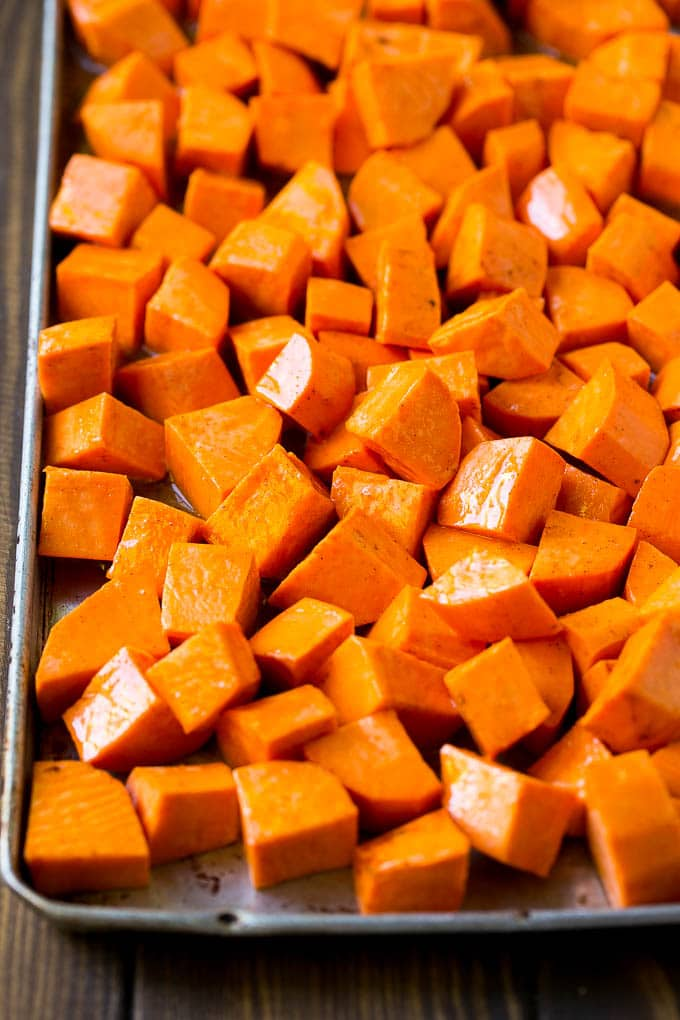Raw diced sweet potatoes on a sheet pan, ready to go into the oven.
