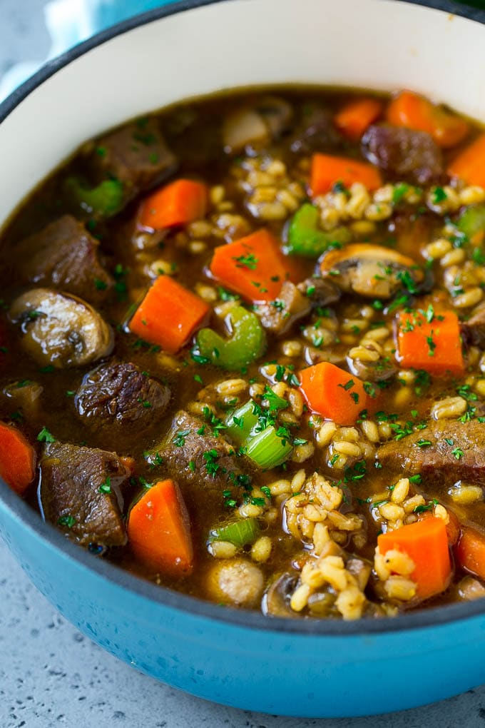 A pot of beef barley soup with mushrooms, carrots and celery.