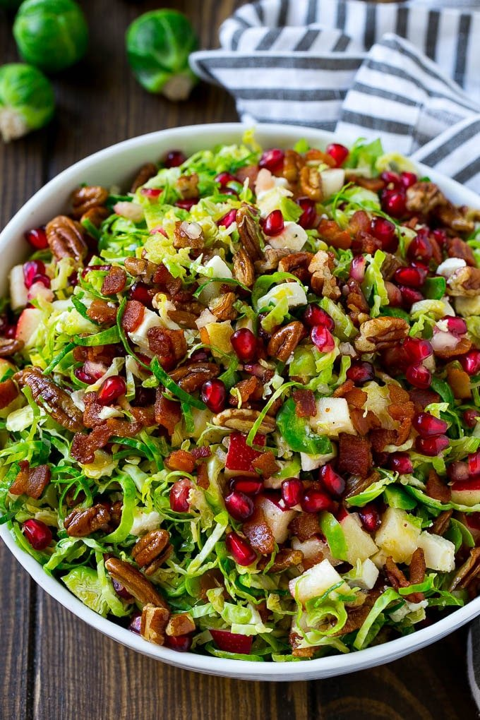 A bowl of brussels sprout salad made with pomegranate, bacon and apples.