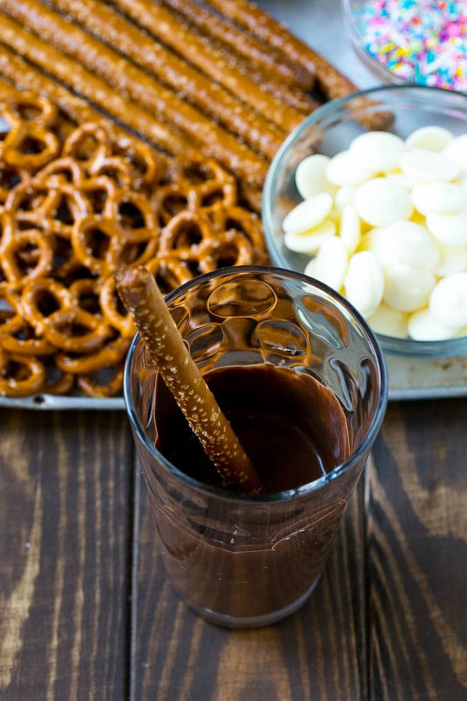 A pretzel rod in a glass full of melted chocolate.