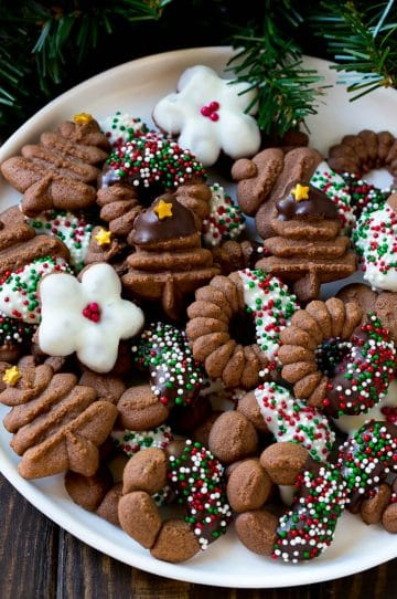 A plate of chocolate spritz cookies decorated with chocolate and sprinkles.