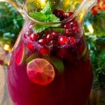 Christmas punch in a pitcher garnished with fresh cranberries, limes and mint.