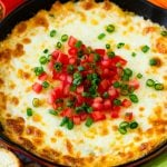 Hot crab dip in a skillet topped with tomatoes and green onions.