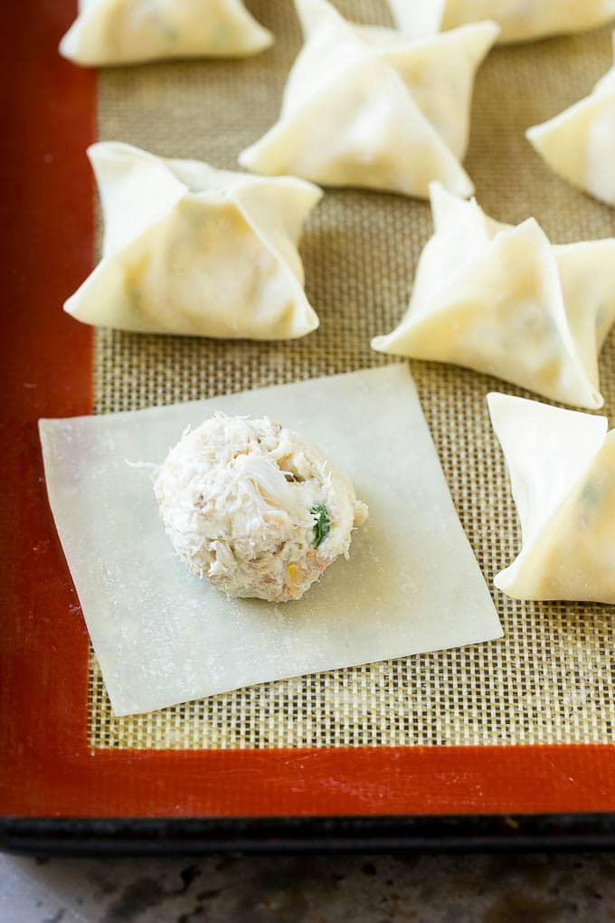 A wonton wrapper with a dollop of crab and cream cheese filling on it.