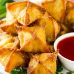 A pile of crab rangoon wontons filled with a creamy crab mixture.