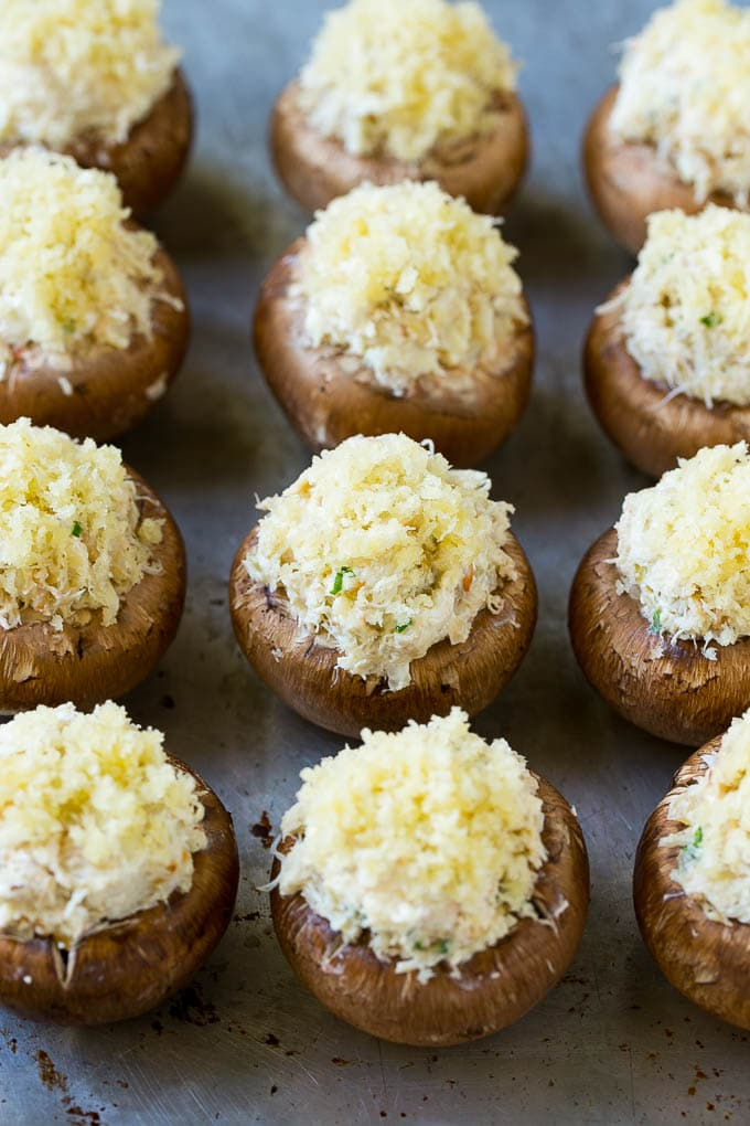 Uncooked crab stuffed mushrooms on a sheet pan.