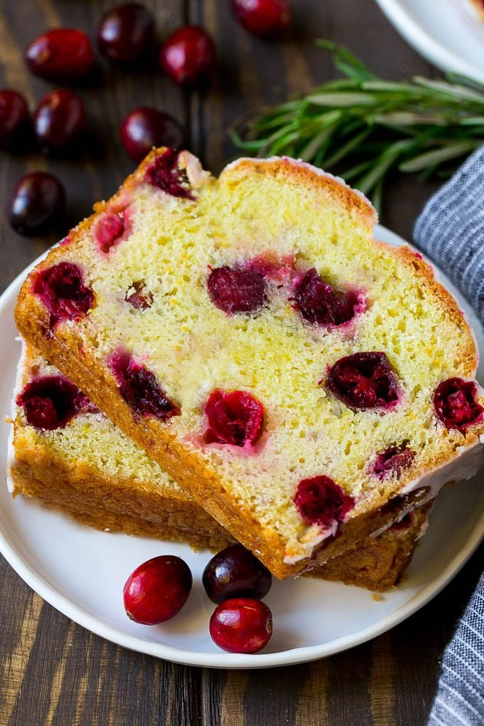 A plate with two slices of cranberry bread and fresh cranberries for garnish.
