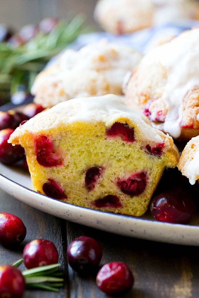 A plate of cranberry muffins with one cut in half.