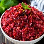 A bowl of cranberry relish topped with whole cranberries, orange zest and mint.