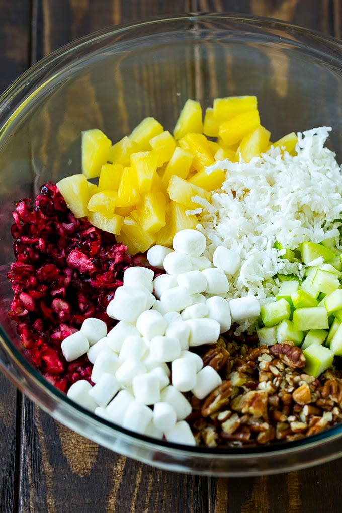 Chopped cranberries, apples, pineapple, marshmallows, pecans and coconut in a mixing bowl.