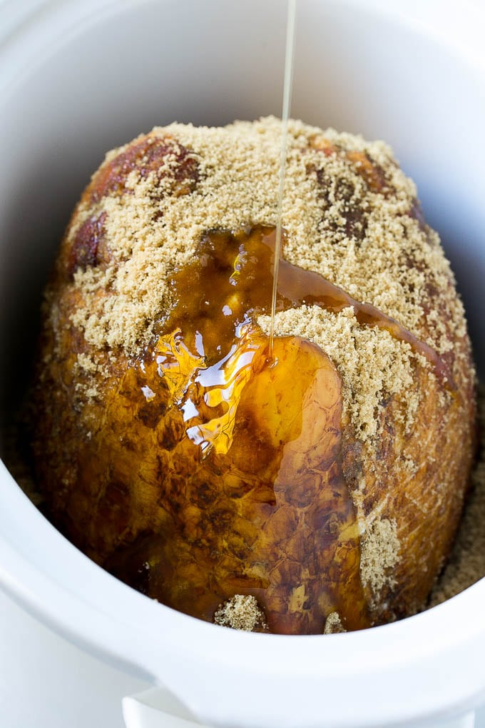 A crock pot ham with maple syrup being poured over the top.