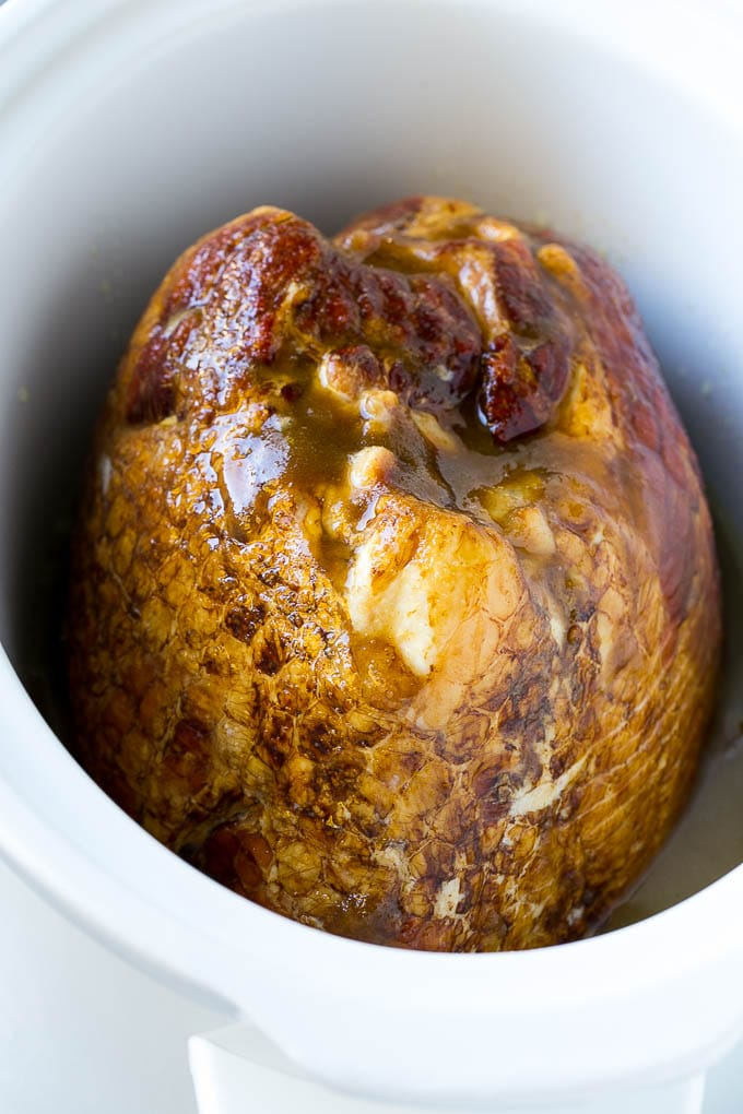 A ham in a slow cooker covered in brown sugar, maple syrup and pineapple juice.