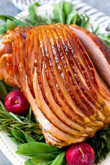 A crock pot ham on a serving plate with herbs and apples for garnish.