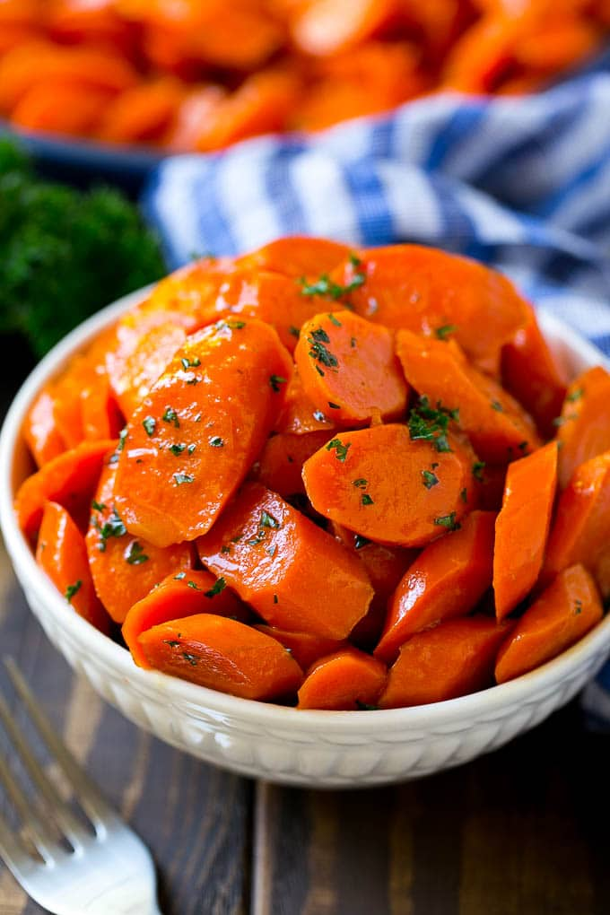 A bowl of glazed carrots topped with parsley.