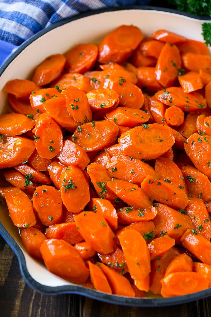 A skillet of glazed carrots with brown sugar and butter sauce.