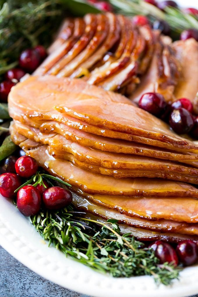 Sliced glazed ham on a serving platter, garnished with herbs and fresh cranberries.