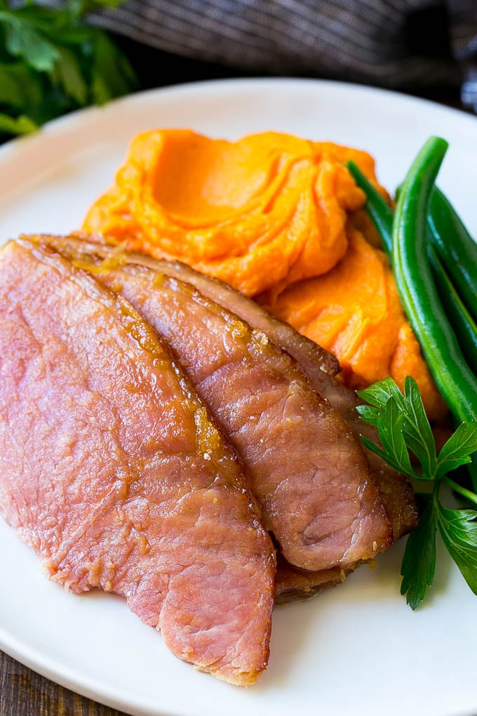 Mashed sweet potatoes on a plate with sliced ham and green beans.