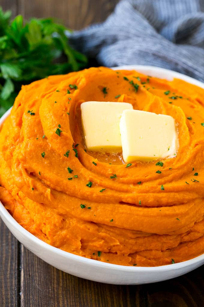 A bowl of mashed sweet potatoes topped with butter and parsley.