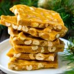 A stack of peanut brittle pieces on a serving plate.