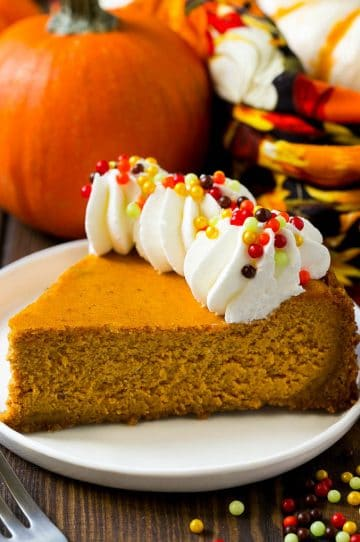 A slice of pumpkin cheesecake on a graham cracker crust, topped with whipped cream and sprinkles.