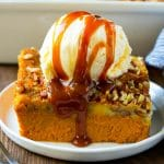 A slice of pumpkin dump cake topped with ice cream and caramel sauce.