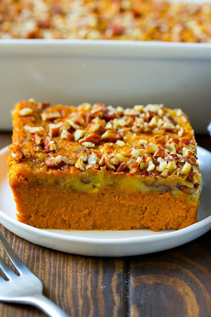 A slice of pumpkin dump cake topped with pecans.