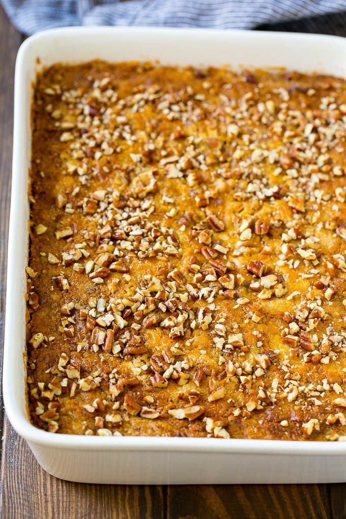 A pan of pumpkin dump cake topped with chopped pecans.