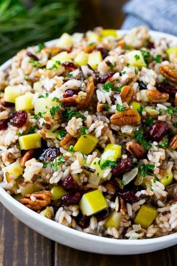 A serving bowl of rice pilaf made with wild rice, apples, cranberries and pecans.
