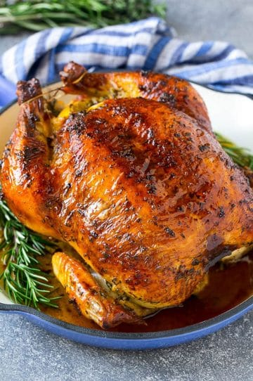 A roasted chicken in a pan garnished with fresh rosemary sprigs.