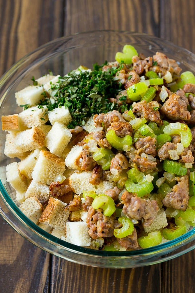 Sausage, sauteed vegetables and bread cubes in a mixing bowl.