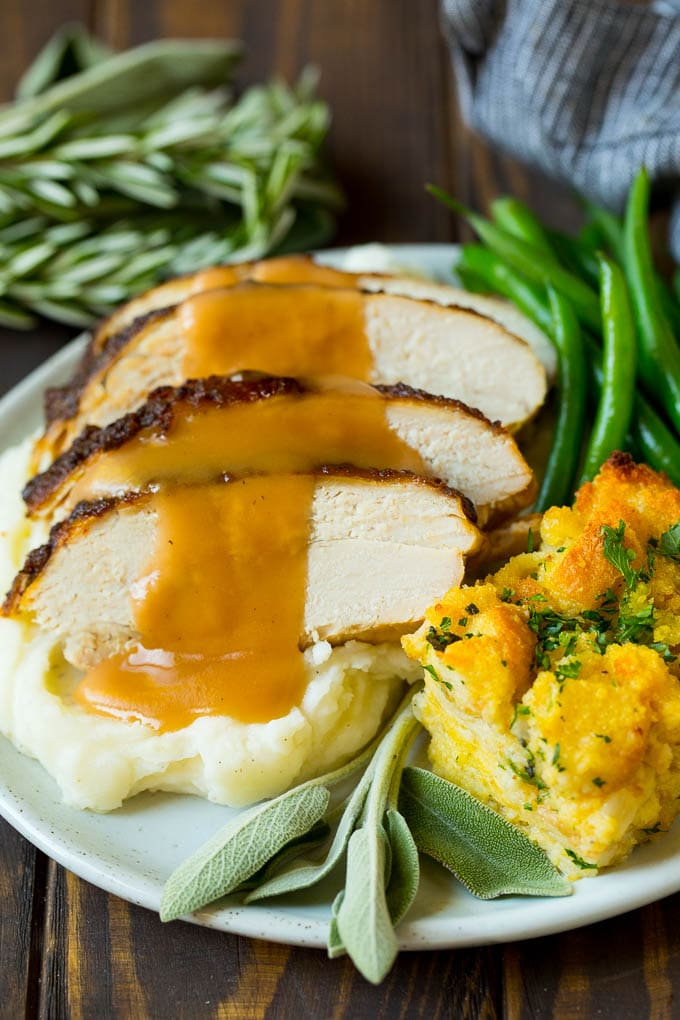 Sliced slow cooker turkey breast served with stuffing and green beans.