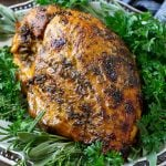 A slow cooker turkey breast on a serving platter with fresh herbs.