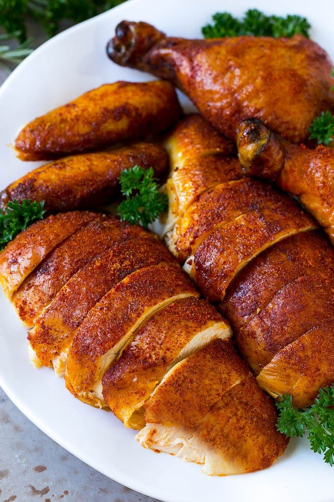 Carved smoked chicken including drumsticks, wings and chicken breasts on a serving platter.
