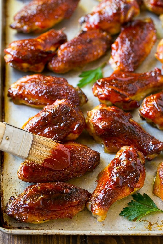 BBQ sauce brushed onto a sheet pan of smoked chicken wings.