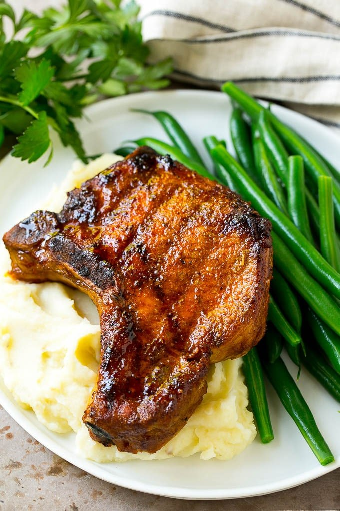 Smoked pork chops over mashed potatoes with green beans on the side.