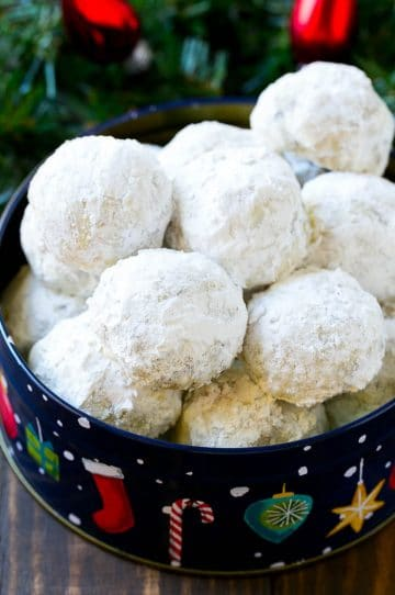 Snowball cookies coated in powdered sugar and served in a holiday tin,