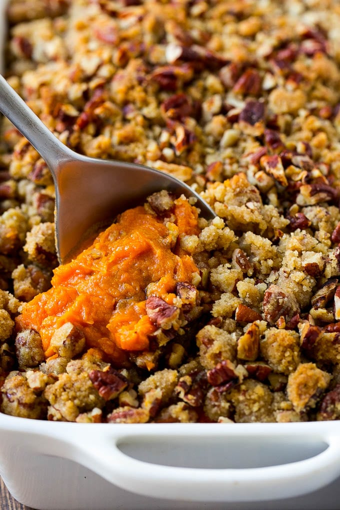 A dish of sweet potato casserole with pecans with a serving spoon in it.