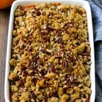 Sweet potato casserole with pecans and brown sugar streusel in a baking dish.