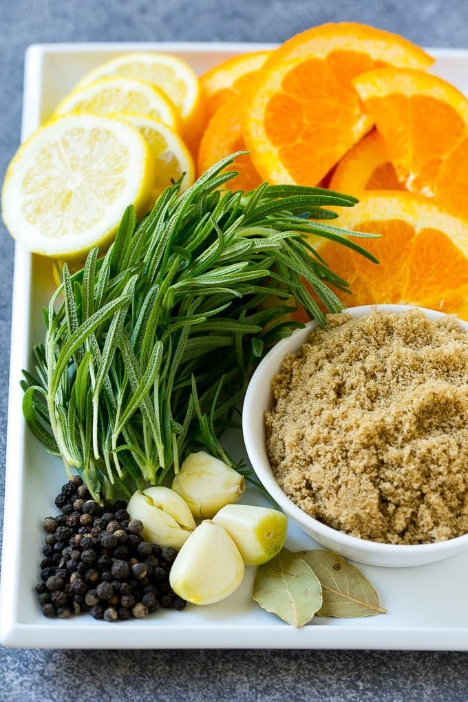 Ingredients for turkey brine including rosemary, brown sugar, oranges, lemons and spices.
