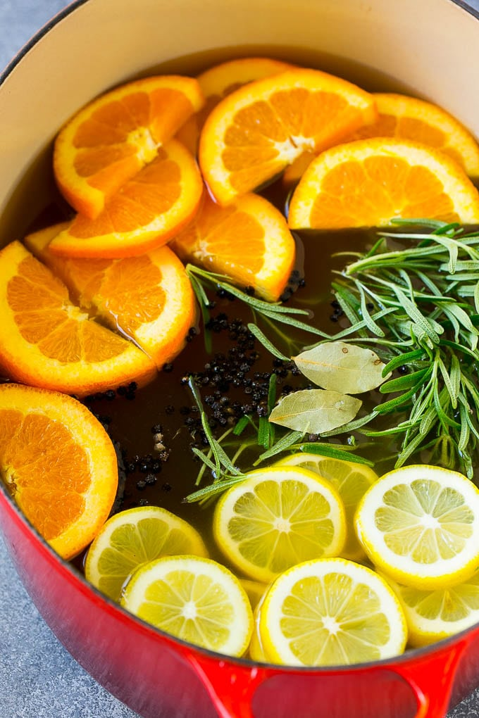 A pot of turkey brine full of citrus, herbs and spices.