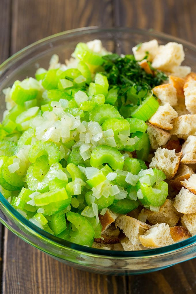 Bread cubes, celery, onion and herbs in a mixing bowl.