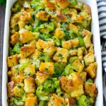 Baked turkey stuffing in a dish topped with fresh parsley.