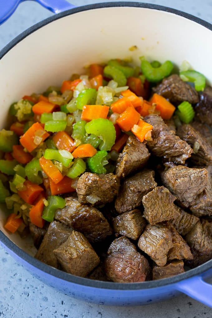 Beef stew meat, carrots, onion and celery in a pot.