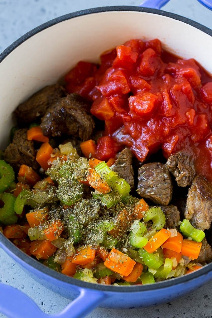Beef chunks, vegetables, tomatoes and herbs in a pot.