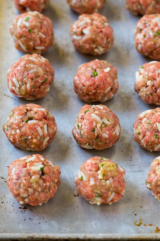 Uncooked beef and rice meatballs on a sheet pan.